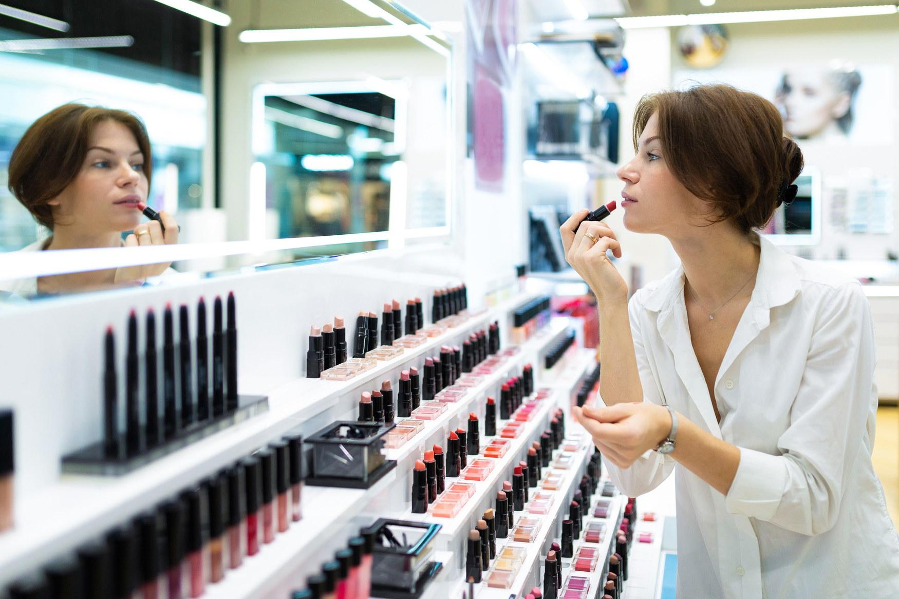 若い女性は、化粧品店で赤い口紅を置く