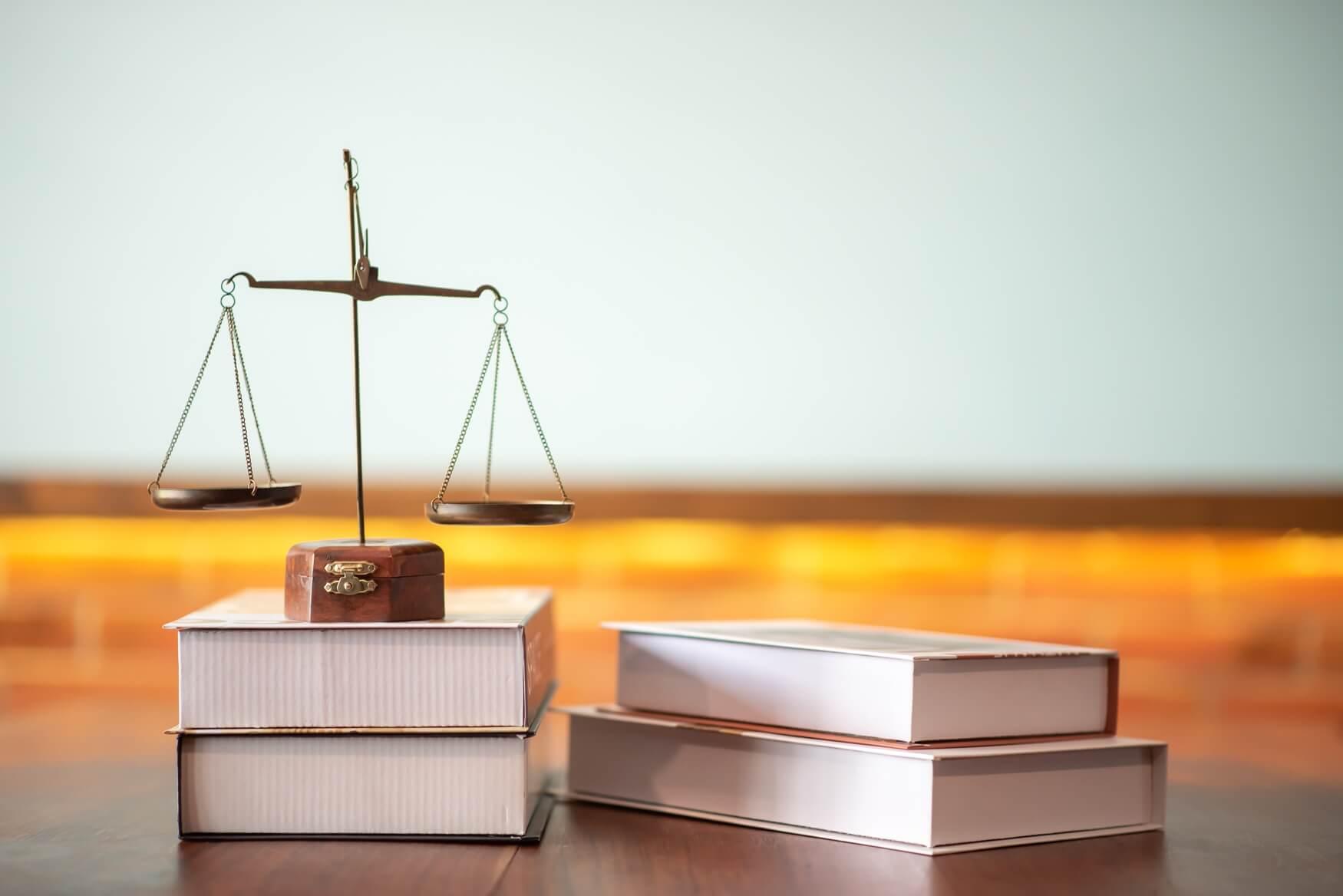法廷のテーブルに正義と法的な本のクローズアップ