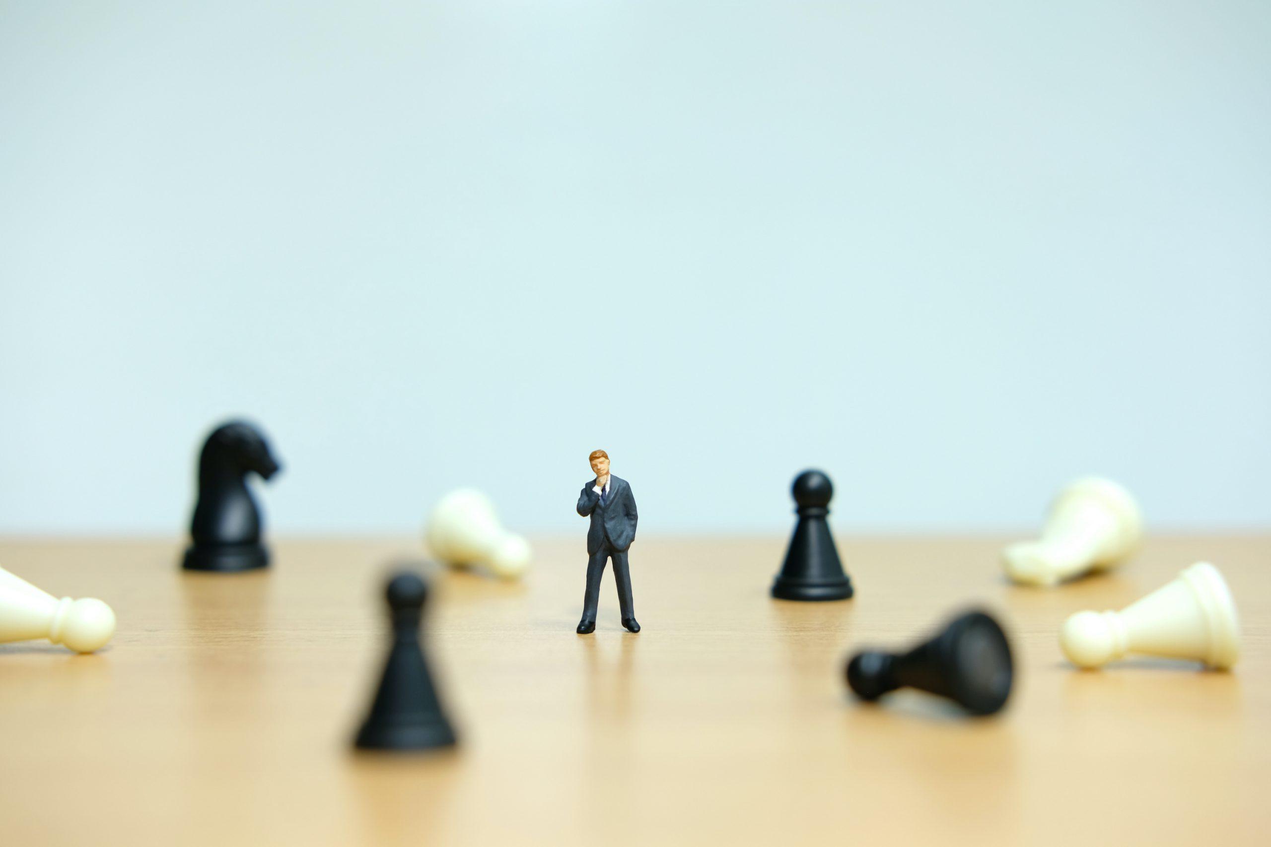 チェスのポーンの真ん中に立っているビジネスマン