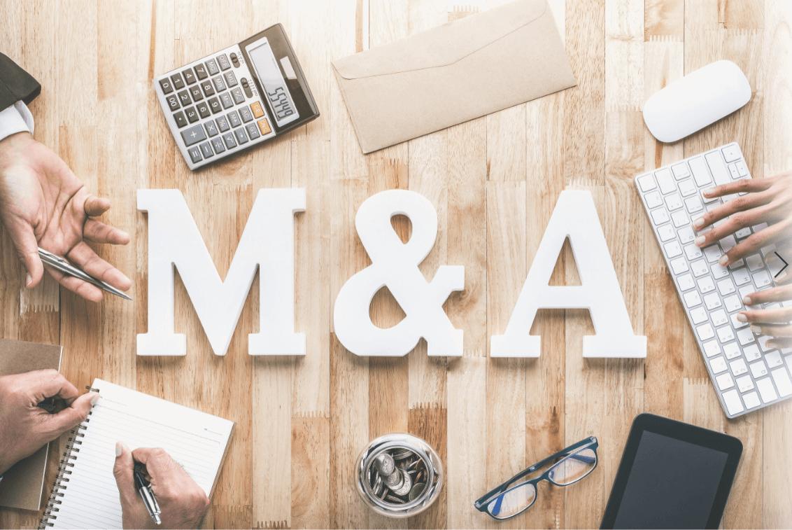 M&Aの文字と会議中のテーブル