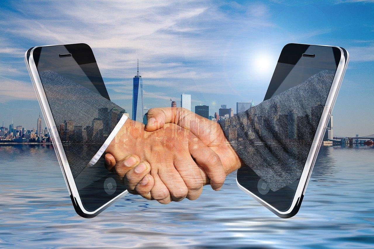 都市とスマホと握手の合成写真
