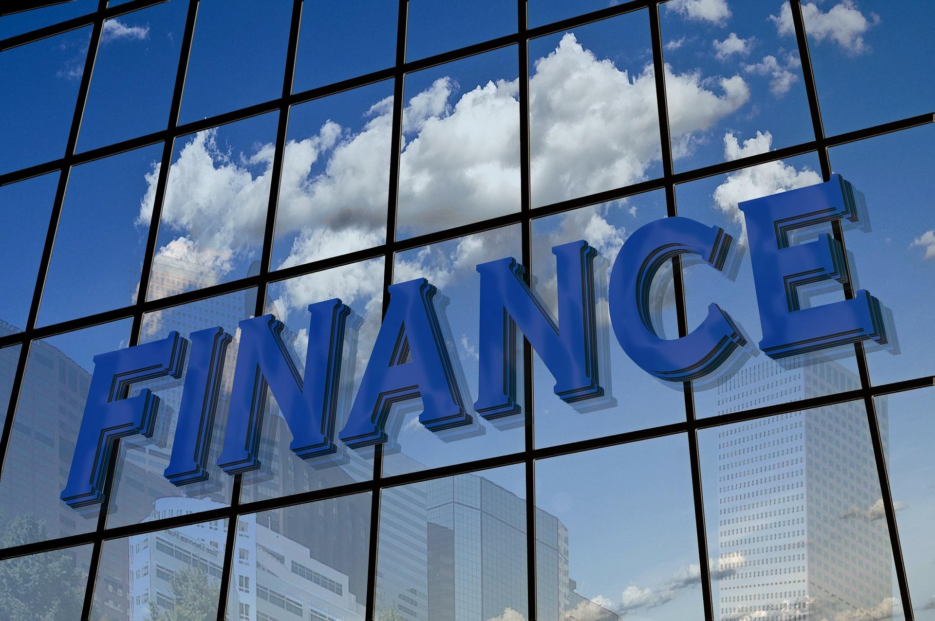 FINANCEの文字が浮かび上がるビルの窓に映る白い雲