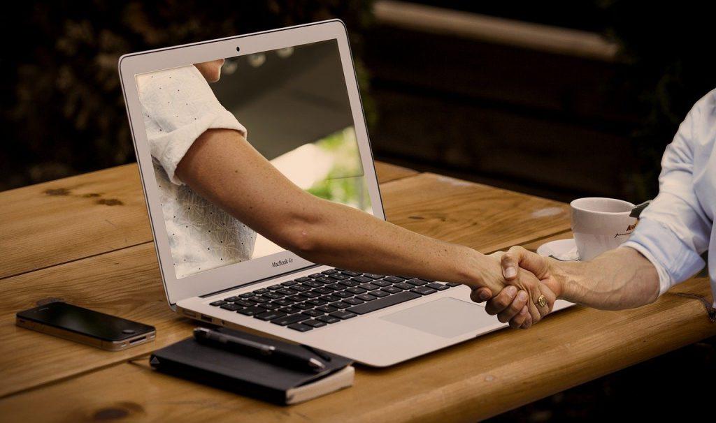 ノートパソコンのモニターから伸びる手との握手